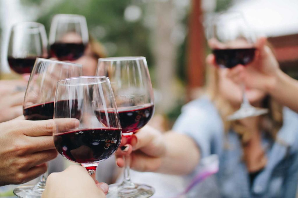 People enjoying red wine in the sunlight